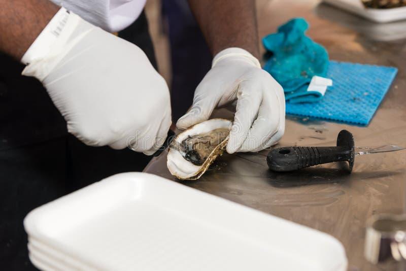 Traiteur die een mariene oester pellen royalty-vrije stock afbeeldingen