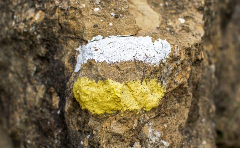 Traits horizontaux blancs et jaunes sur une roche détaillée comme signe du chemin images libres de droits