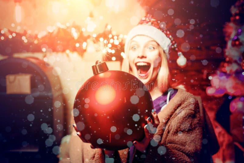 Traje alegre de la Navidad de la mujer que lleva joven sobre la pared de madera Mujer con el regalo del regalo de Navidad fotografía de archivo