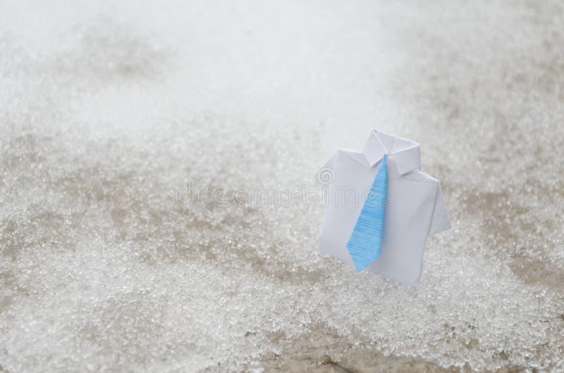 Traje blanco de la papiroflexia del negocio con el lazo azul en la tierra de la nieve fotografía de archivo