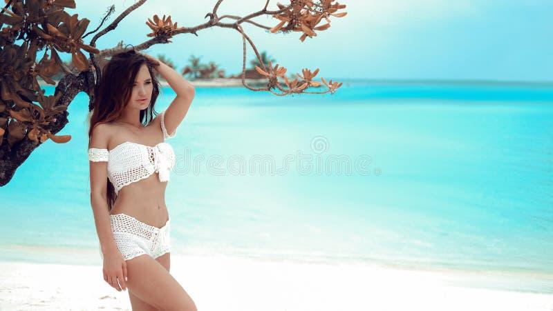 Traje de ba?o blanco del bikini del ganchillo de la muchacha que lleva atractiva hermosa que presenta por el ?rbol en laguna del  fotografía de archivo
