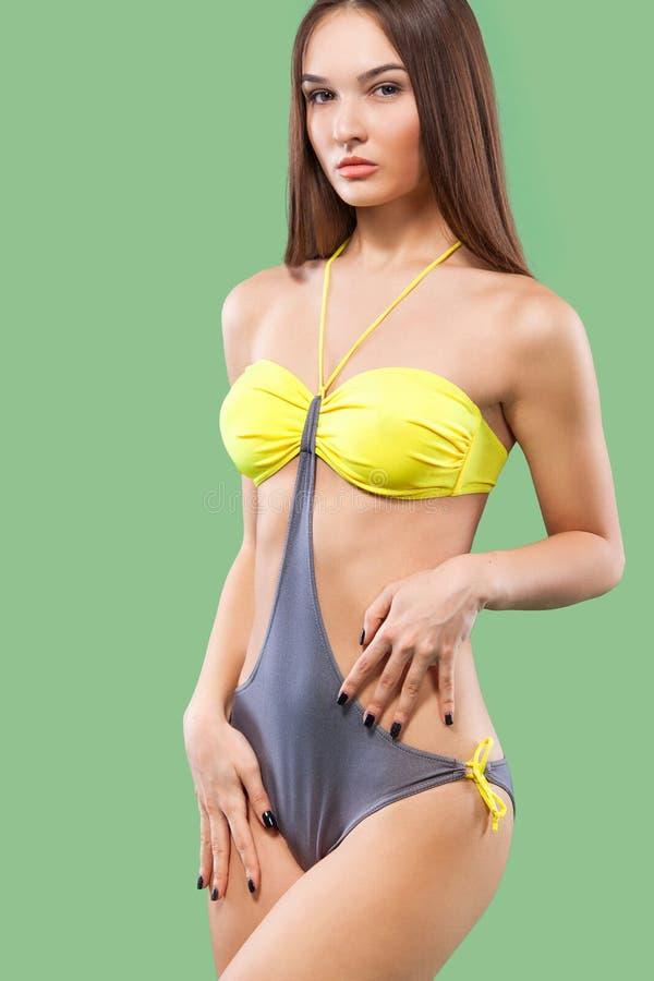 Traje de baño que lleva de la mujer rubia atractiva que presenta en fondo del color Carrocería perfecta Catálogo del bikini foto de archivo