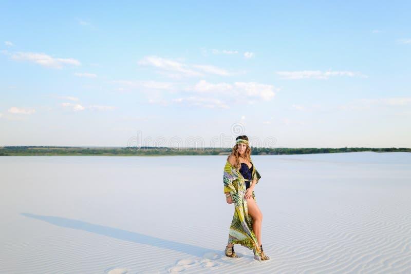 Traje de baño que lleva de la chica joven y traje verde de la playa que se colocan en el san fotografía de archivo libre de regalías