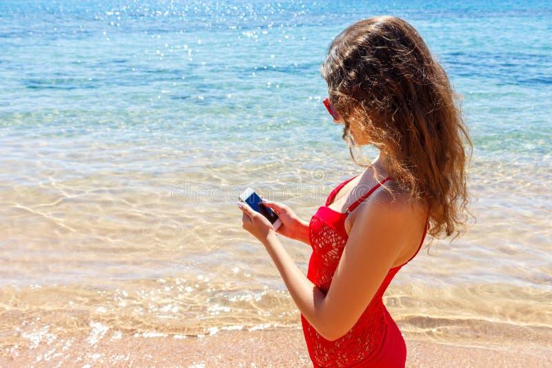 Traje de baño que lleva de la muchacha del persona que toma el sol usando un teléfono elegante Vacaciones de verano en la playa imagen de archivo
