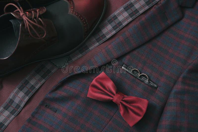 Traje de Borgoña de los hombres, corbata de lazo y zapatos de cuero del vintage en fondo del tweed de la materia textil fotografía de archivo
