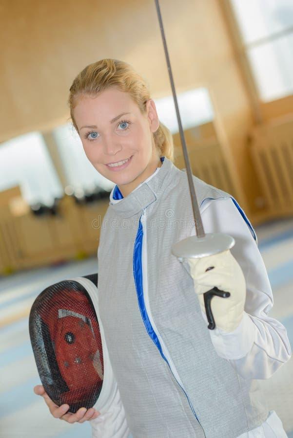 Traje de cercado blanco que lleva de la mujer que practica con la espada fotos de archivo