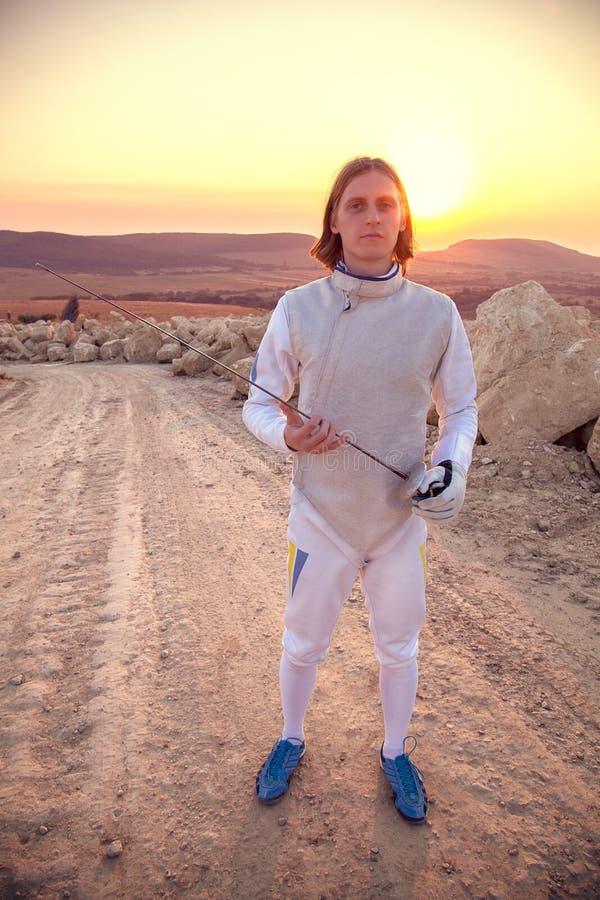 Traje de cerco branco vestindo do homem do esgrimista que guarda a espada e que olha para a frente imagem de stock