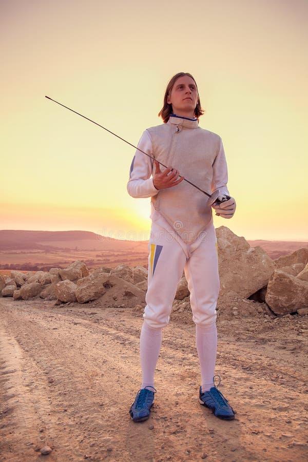 Traje de cerco branco vestindo do homem do esgrimista que guarda a espada e que olha para a frente fotografia de stock royalty free