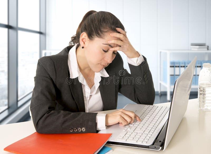 Traje de negocios que lleva de la empresaria que trabaja en el ordenador portátil en el sitio moderno de la oficina foto de archivo