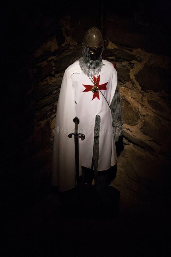 Traje de un templar con la espada en la oscuridad con el fondo de piedra imágenes de archivo libres de regalías