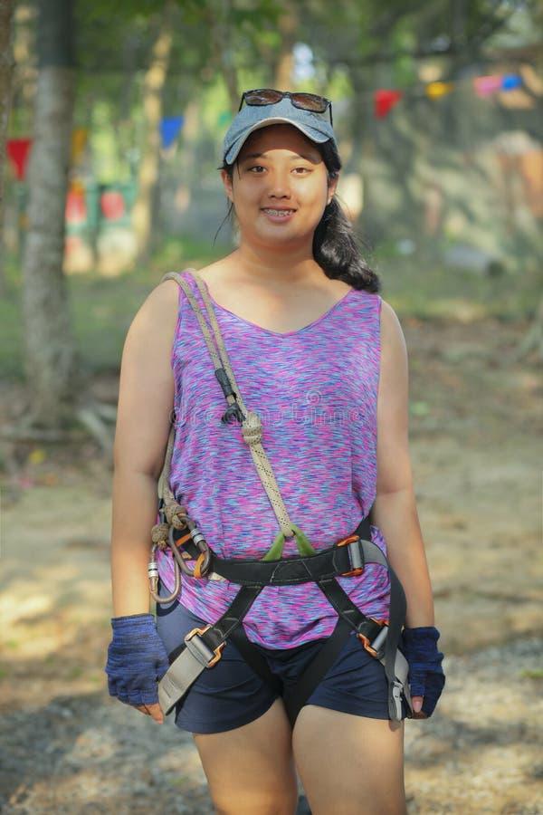 Traje del arnés de seguridad del adolescente que lleva asiático que se prepara para jugar fotos de archivo