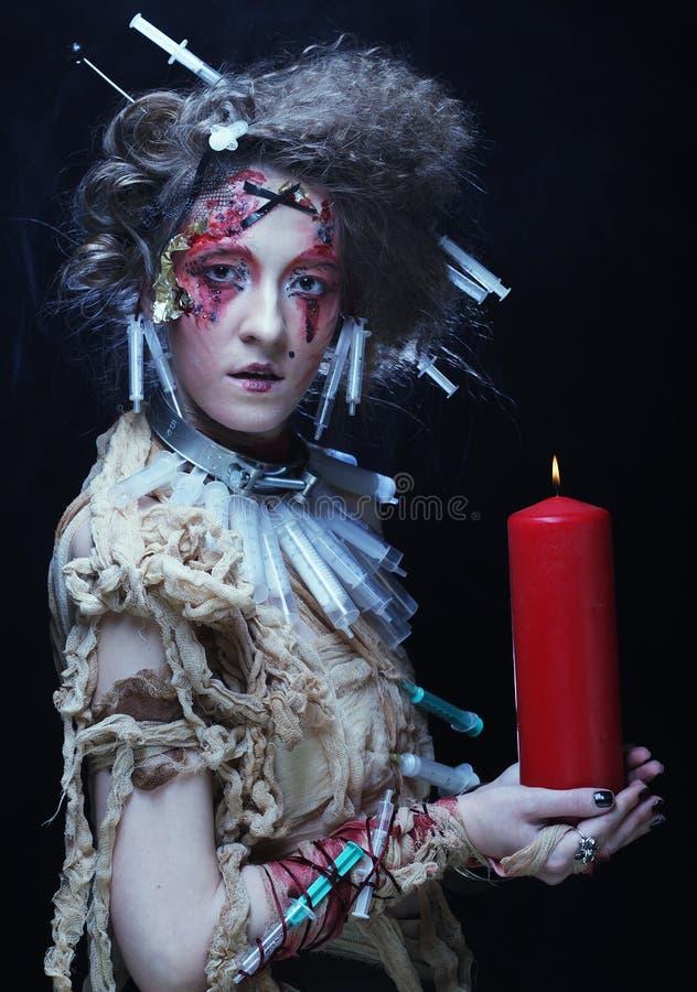 Traje del carnaval de la mujer que lleva joven que lleva a cabo una vela foto de archivo libre de regalías