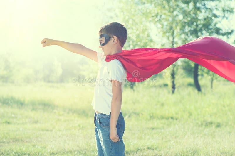 Traje del super héroe del niño pequeño que lleva imagenes de archivo