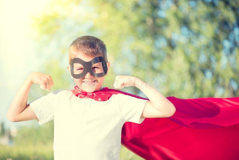 Traje del super héroe del niño pequeño que lleva foto de archivo libre de regalías