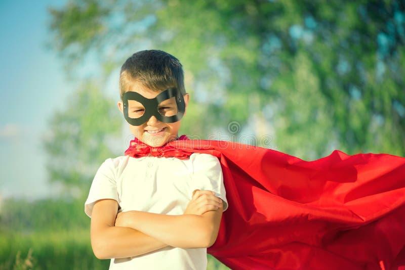 Traje del super héroe del niño pequeño que lleva imágenes de archivo libres de regalías