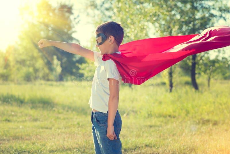 Traje del super héroe del niño pequeño que lleva fotografía de archivo libre de regalías