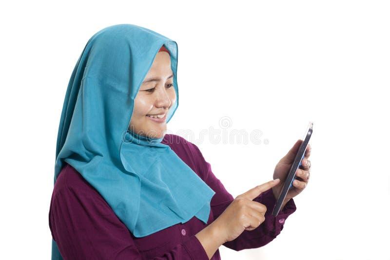 Traje e hijab que llevan con su tableta, expresión sonriente de la empresaria asiática joven Vista lateral aislada en blanco Ciér imágenes de archivo libres de regalías