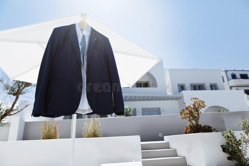 Traje elegante masculino sobre la terraza de un hotel de lujo antes de la ceremonia de matrimonio en la isla de Santorini, Grecia imagen de archivo
