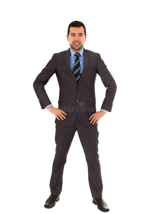 Traje gris que lleva permanente del hombre latino joven foto de archivo