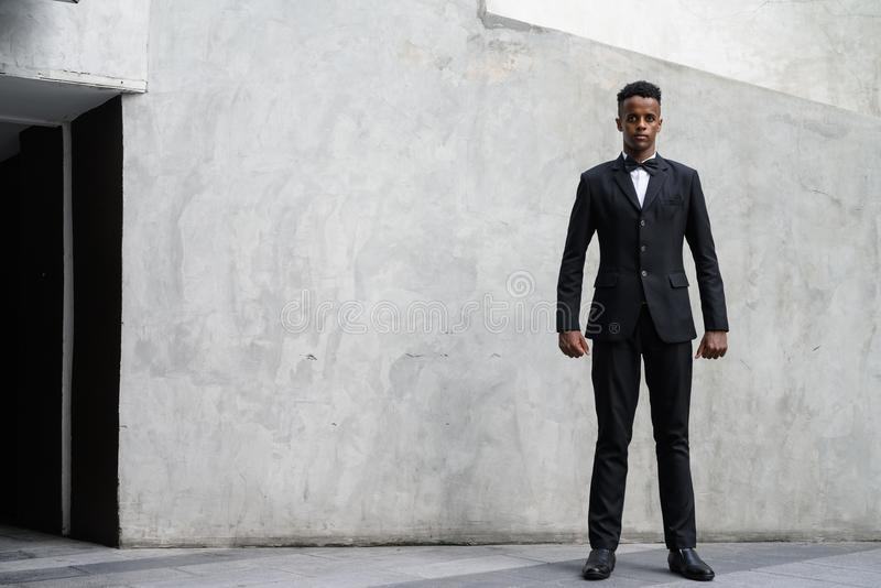 Traje que lleva del hombre de negocios africano hermoso joven contra el hormigón fotos de archivo