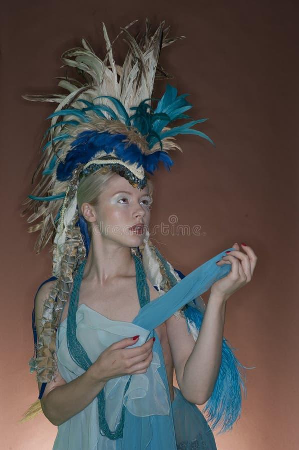 Traje vestindo da jovem mulher bonita com a chapelaria da pena sobre o fundo colorido foto de stock royalty free