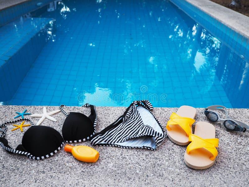 Traje y accesorios de nataci?n de la mujer en el borde de la piscina foto de archivo libre de regalías