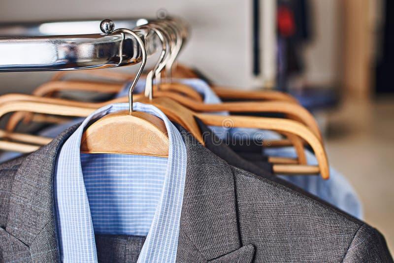 Trajes para hombre y camisas azules formales en suspensiones de madera en una tienda de la ropa fotografía de archivo