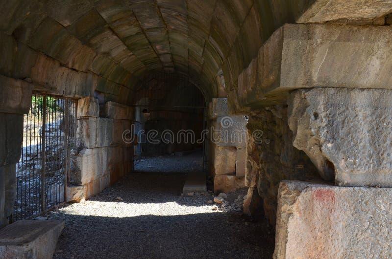 Trajeto através de um túnel arqueado curvado escuro em ruínas de pedra velhas fotografia de stock