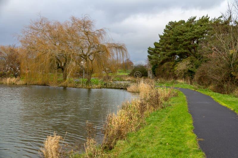 Trajeto curvado ao longo de um lago na Irlanda do parque de Naas fotografia de stock