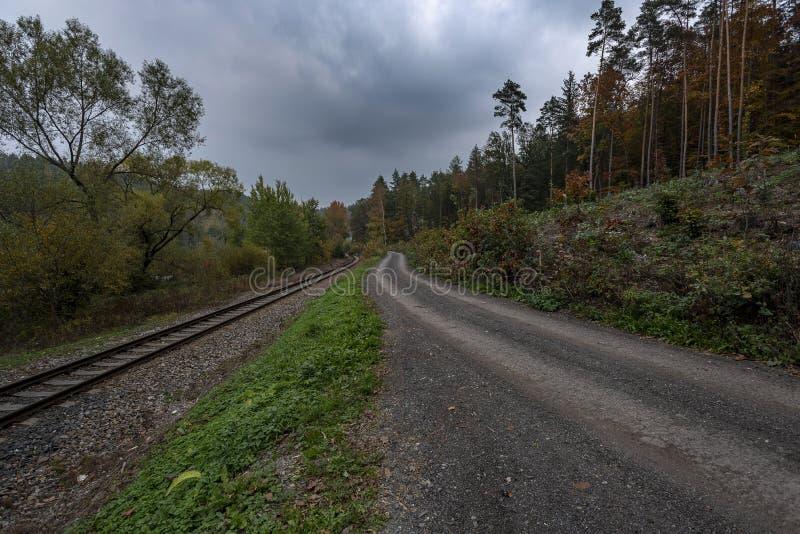 Trajeto de floresta ao lado das trilhas do trem sob nuvens de tempestade imagens de stock