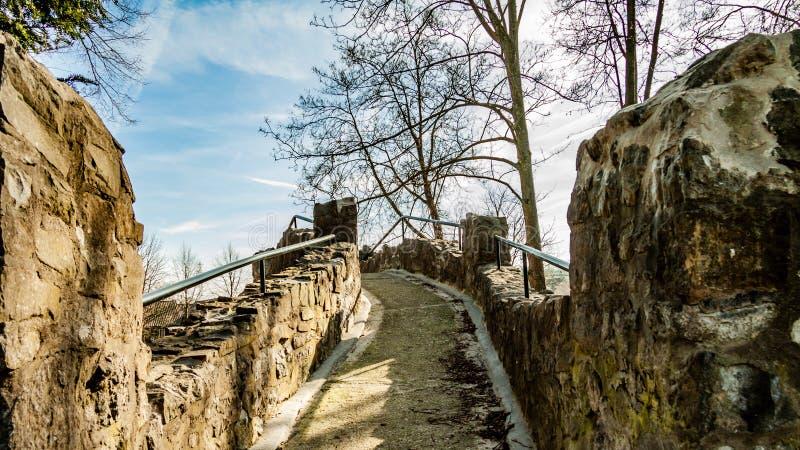 Trajeto de pedra entre as paredes e os trilhos do metal de uma ponte velha imagens de stock