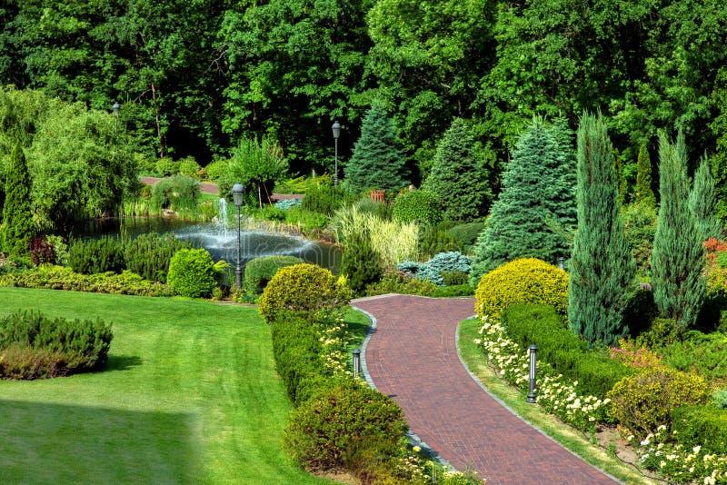 Trajeto do jardim que conduz a uma lagoa com um projeto da fonte e da paisagem fotos de stock royalty free