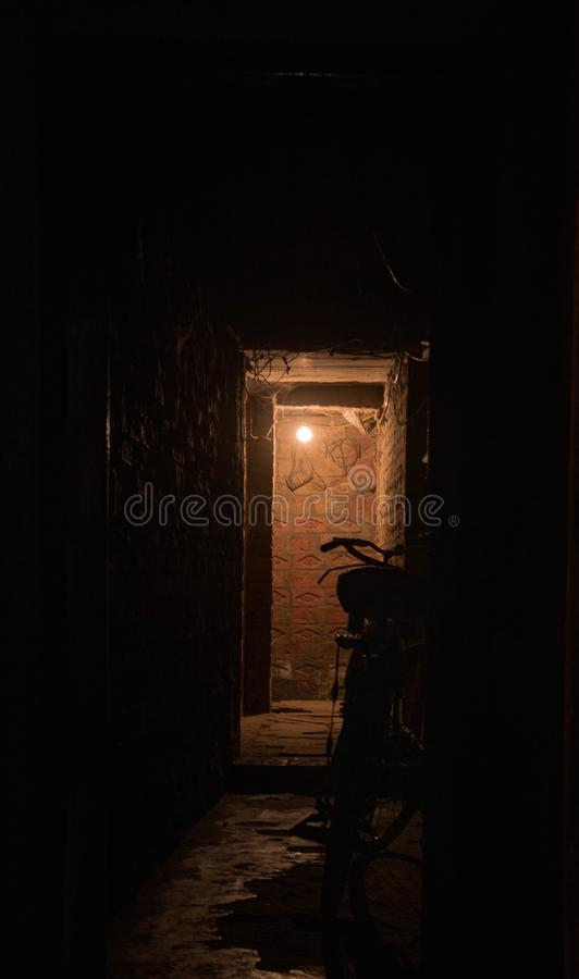 Trajeto escuro iluminado pela única lâmpada fotografia de stock