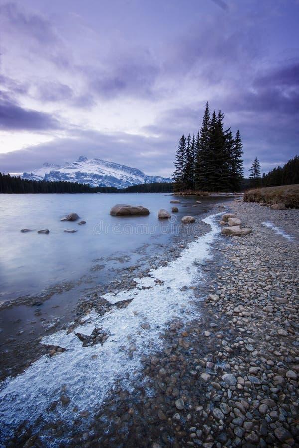 Trajeto gelado ao longo do lago que conduz à ilha pequena com árvores e a montanha coberto de neve alta atrás, pa nacional do lag imagem de stock