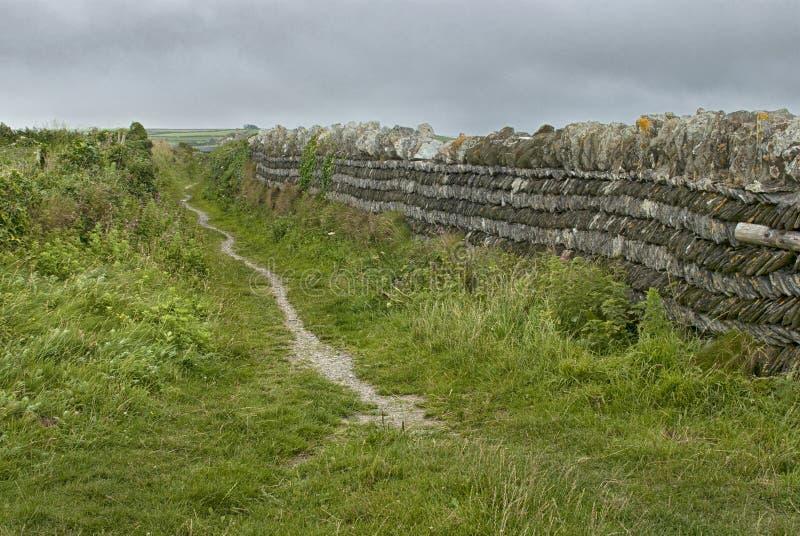 Trajeto litoral ao lado de uma cerca de pedra córnico fotos de stock royalty free