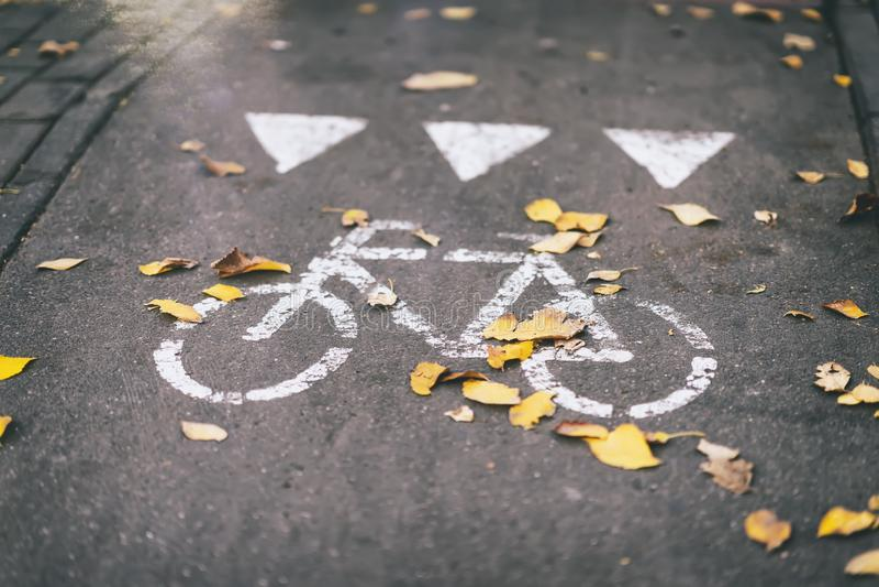 Trajeto na cidade, queda do outono da rua da folha, folhas no passeio, bicicleta, sinal de estrada imagem de stock