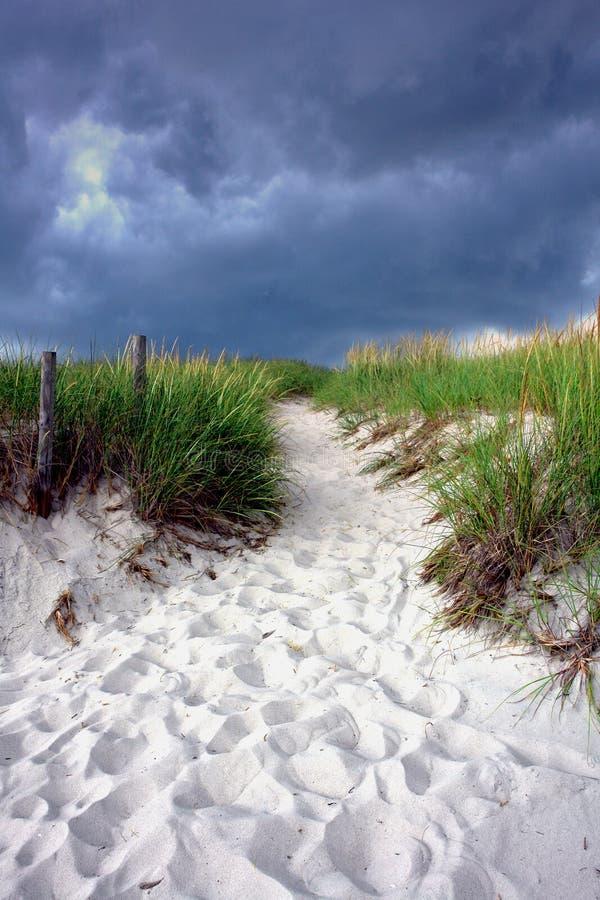 Trajeto na duna de areia sob o céu tormentoso foto de stock
