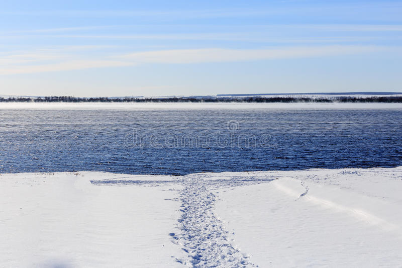 Trajeto pisado na neve à água Lago não congelado no inverno foto de stock royalty free