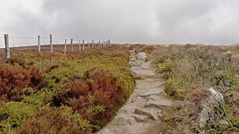 Trajeto rochoso ao longo de uma cerca na parte superior fora das montanhas nevoentas de Ticknock com charneca imagem de stock