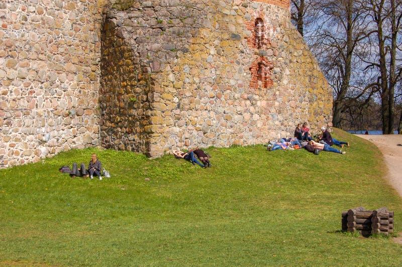 Trakai Litauen, 30-04-2017 Folket ligger på gräset och värma sig på våren solen nära väggarna av den gamla slotten Trakai arkivbilder