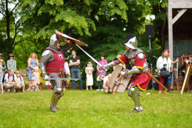 TRAKAI, LITOUWEN - JUNI 16, 2018: Mensen die de strijd van ridderkostuums dragen tijdens het historische weer invoeren op jaarlij stock foto