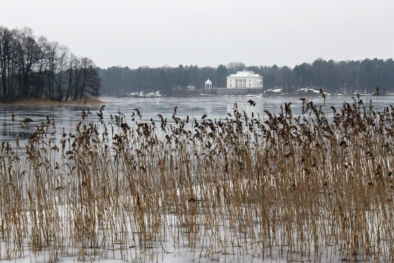 TRAKAI, LITUÂNIA - 2 DE JANEIRO DE 2013: Opinião do inverno solar residencial do lago Galve do antigo e do palácio de Uzutrakis fotografia de stock royalty free