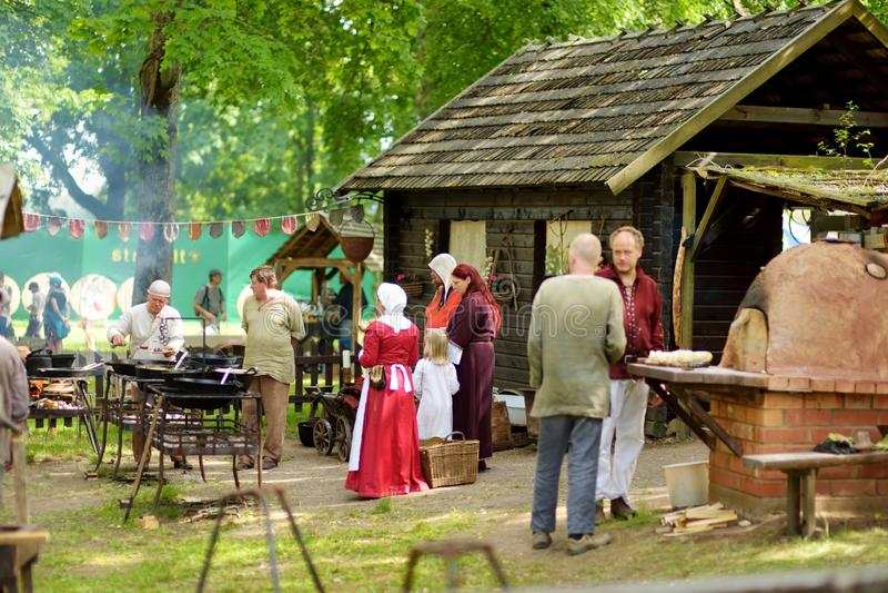 TRAKAI, LITUÂNIA - 16 DE JUNHO DE 2018: Ativistas históricos do reenactment que preparam o alimento sobre um fogo aberto durante  imagens de stock royalty free