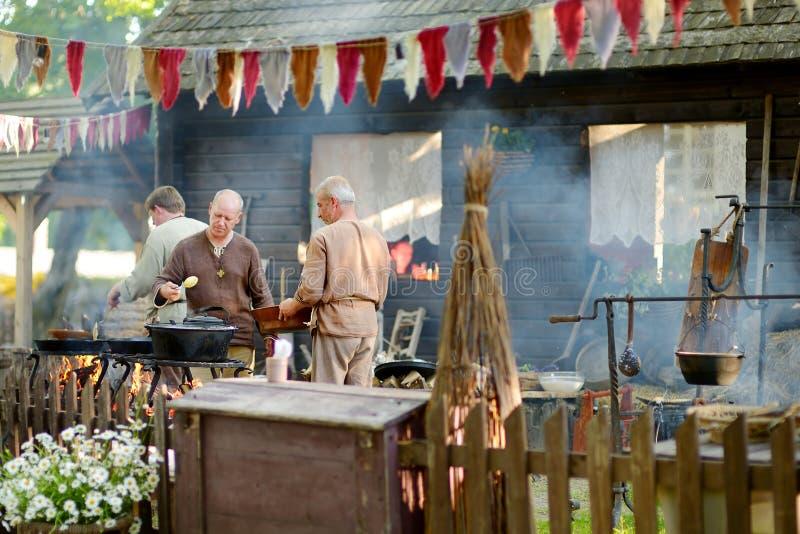 TRAKAI, LITUÂNIA - 16 DE JUNHO DE 2018: Ativistas históricos do reenactment que preparam o alimento sobre um fogo aberto durante  foto de stock royalty free