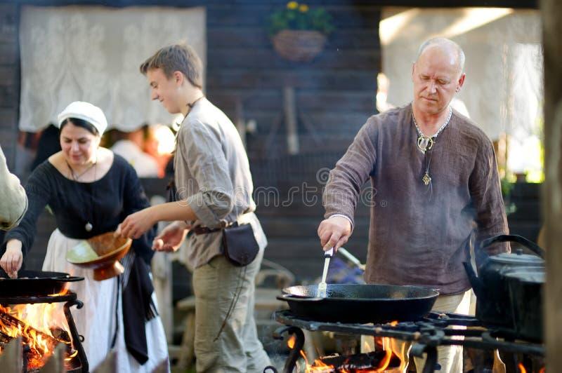 TRAKAI, LITUÂNIA - 16 DE JUNHO DE 2018: Ativistas históricos do reenactment que preparam o alimento sobre um fogo aberto durante  imagens de stock