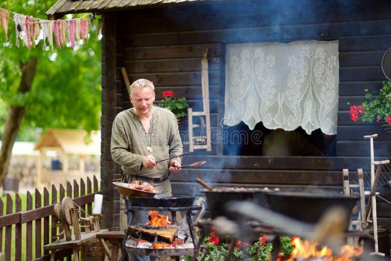 TRAKAI, LITUÂNIA - 16 DE JUNHO DE 2018: Ativistas históricos do reenactment que preparam o alimento sobre um fogo aberto durante  fotos de stock