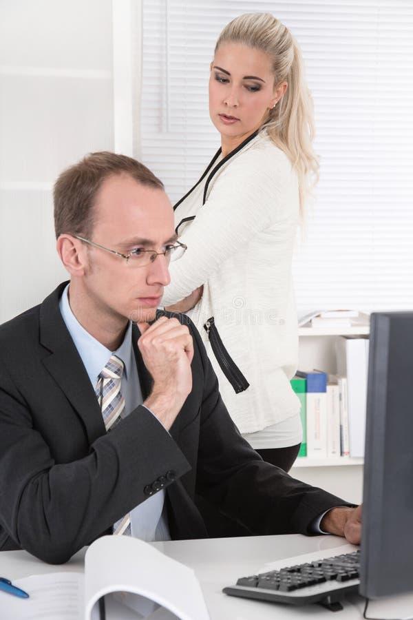Trakassera - problem under kollegor på kontoret. royaltyfri bild