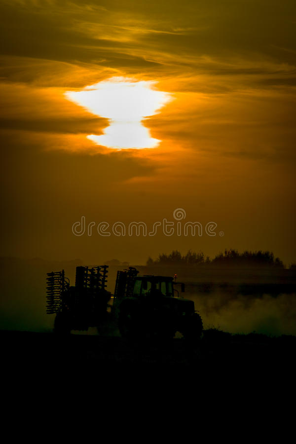 Traktor auf dem Feld während des Sonnenuntergangs stockbild
