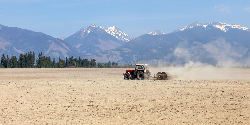 Traktor, der im Frühjahr Rollen über trockenen Feldern, Gebirgsesprit zieht stockfoto