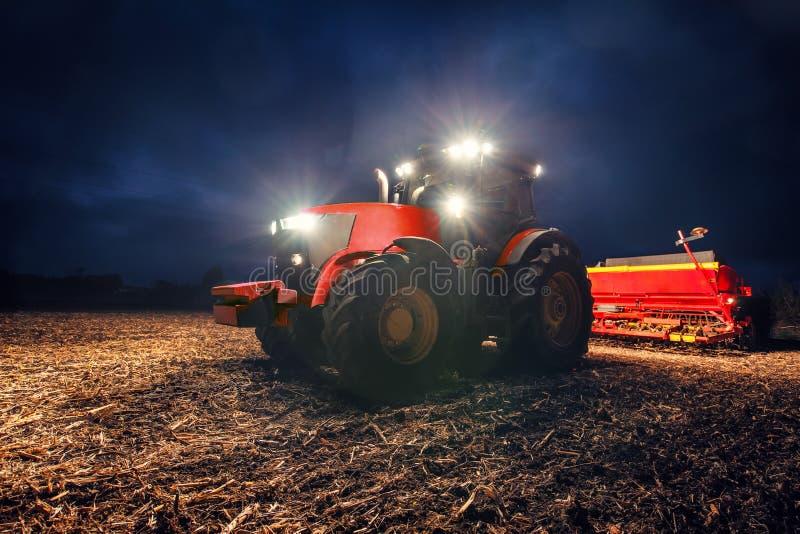 Traktor, der Land mit Saatbeetlandwirt nachts vorbereitet lizenzfreie stockfotografie